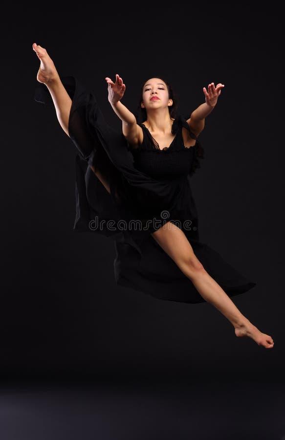 Utalentowany dziewczyna tancerz w czarnym smokingowym doskakiwaniu w górę podesłania iść na piechotę w dratwie Czarny tło zdjęcie stock