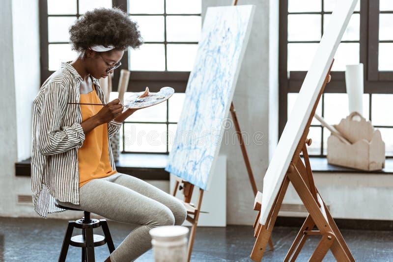 Utalentowany młody artysta miesza guasz na małej kolor palecie obraz royalty free