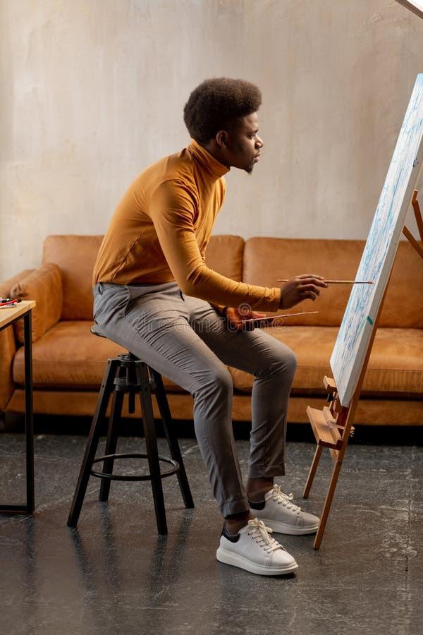 Utalentowany młody człowiek patrzeje kanwę obraz stock