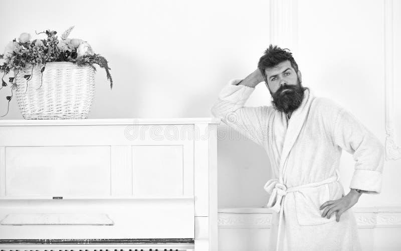 Utalentowany muzyka pojęcie Mężczyzna z brodą w bathrobe cieszy się ranek podczas gdy stojący blisko pianina Mężczyzna poważni st zdjęcia stock