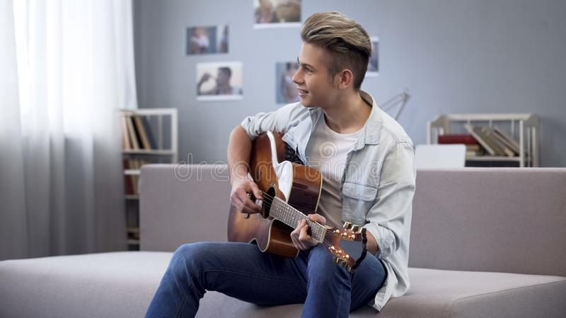 Utalentowany nastolatek bawić się gitarę, szkoła wyższa facet cieszy się melodię dla jego nowej piosenki fotografia stock
