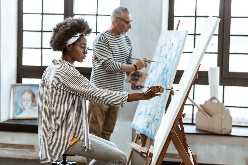 Utalentowany obiecujący żeński artysta pracuje blisko jej nauczyciela obraz stock