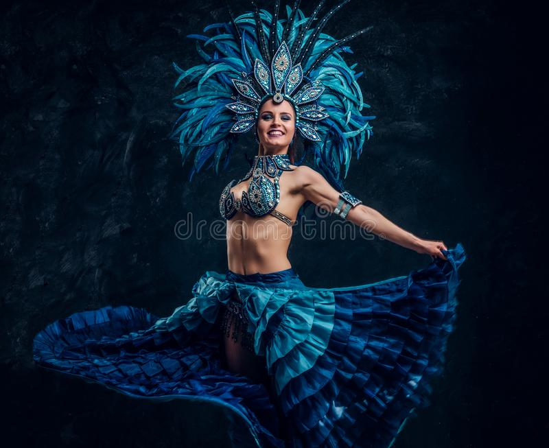 Utalentowany radosny tancerz w czerwieni piórka kostiumu pozuje przy małym ciemnym studiiem obrazy stock