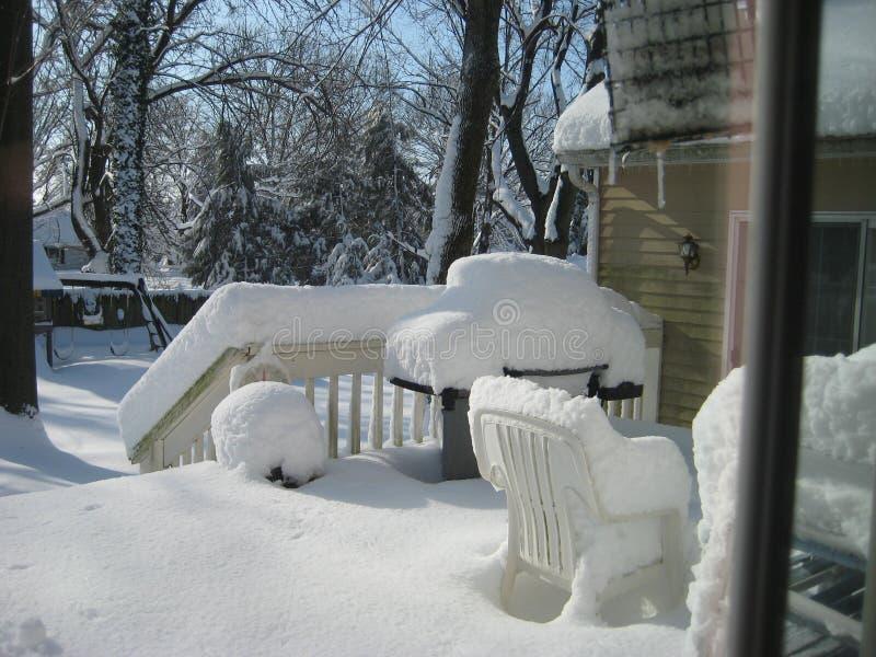 Utanför tillbaka däck av huset efter snöstorm arkivbilder