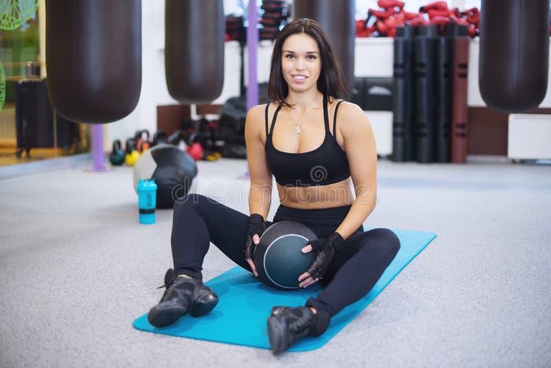 Utarbeta konditionkvinnan som övar med medecinebollen i idrottshallen som smilling och ser kameran royaltyfria foton