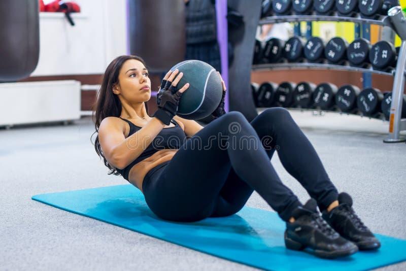 Utarbeta konditionkvinnan som att göra sitter ups buk- abs arkivbild
