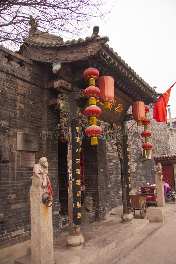 Utarbetad ing?ng till ett forntida kinesiskt hus med skulpturer, r?da lyktor, handstilar i guld och en r?d flagga beijing porslin fotografering för bildbyråer