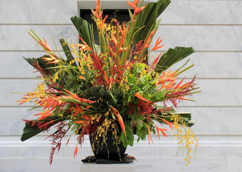 Utarbetad vas som fylls med exotisk blommaordning arkivbild