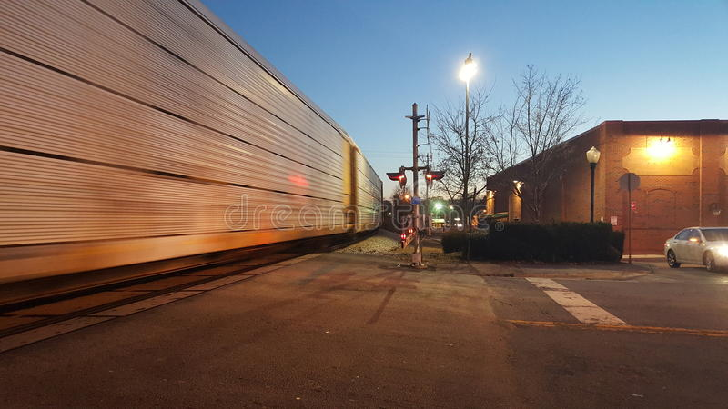 Utbilda flyttningen förbi järnvägkorsning på skymning 2 royaltyfri foto