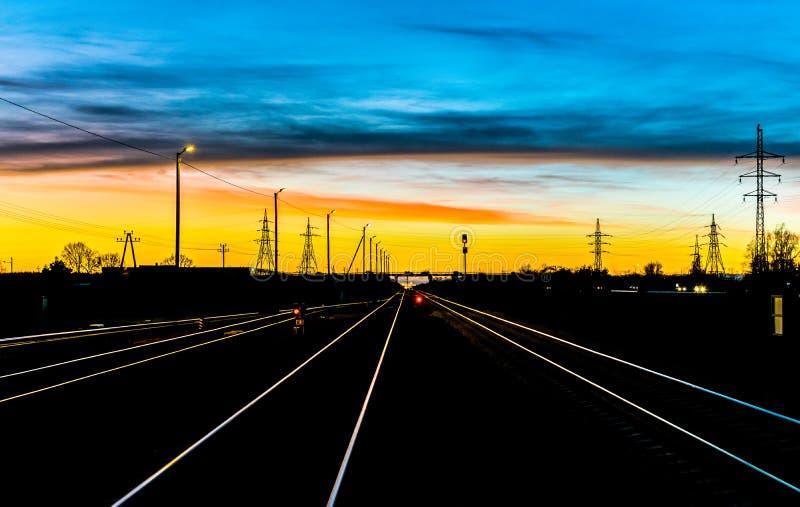 Utbilda spår och elektricitetspyloner som leder av in i avståndet av en solnedgång arkivbilder