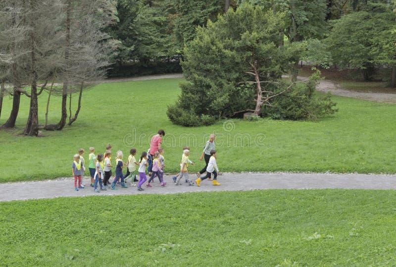 Utbildare med en grupp av förskole- barn i parkera royaltyfri bild