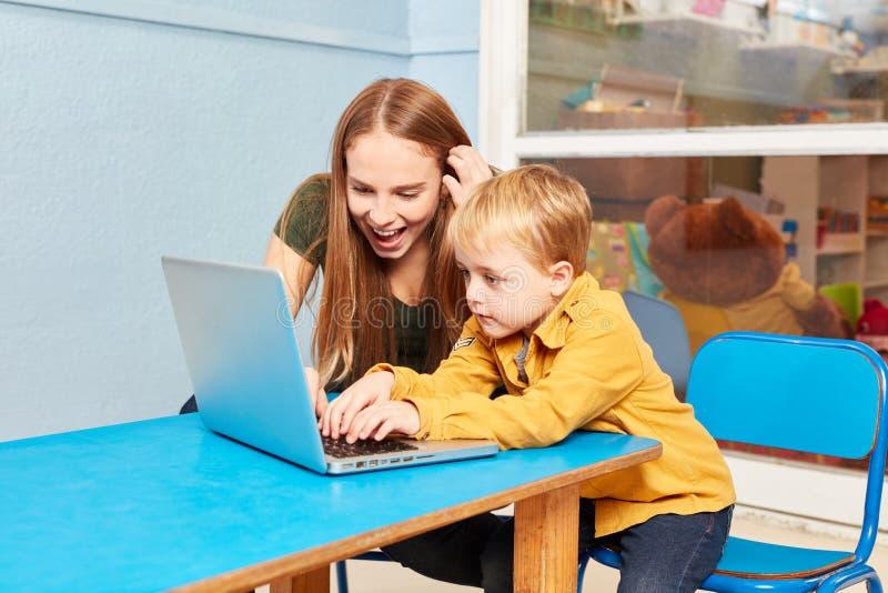 Utbildare och pojke på bärbar datordatoren royaltyfri bild