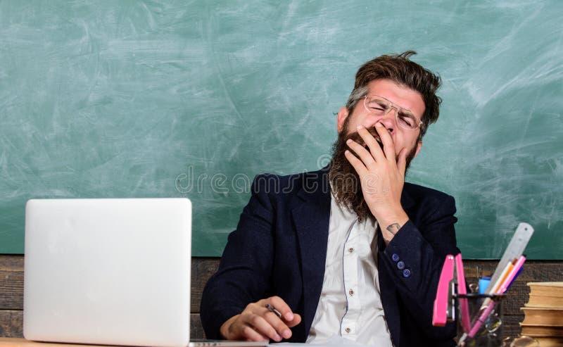 Utbildare som är mer stressad på arbete än genomsnittligt folk På hög nivå trötthet Utbildaren uppsökte mannen som gäspar framsid arkivbild