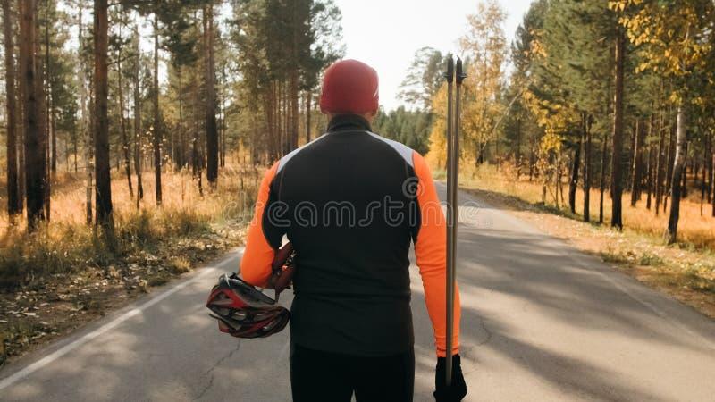 Utbildning av en idrottsman nen på rullskateboradåkarna Biathlonritten på rullskidorna med skidar poler, i hjälmen Höst arkivbilder