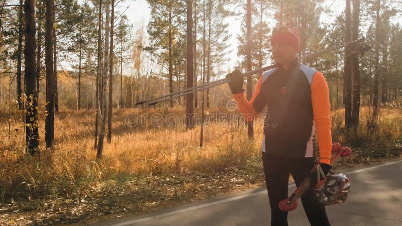Utbildning av en idrottsman nen på rullskateboradåkarna Biathlonritten på rullskidorna med skidar poler, i hjälmen Höst arkivfoton