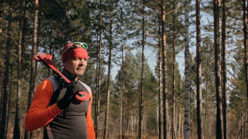 Utbildning av en idrottsman nen på rullskateboradåkarna Biathlonritten på rullskidorna med skidar poler, i hjälmen Höst royaltyfria foton