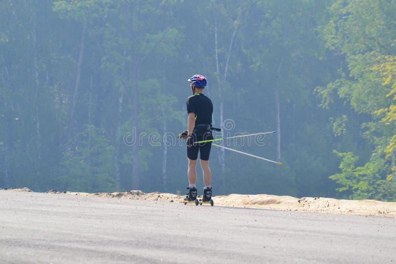 Utbildning av en idrottsman nen p? rullskateborad?karna Biathlonritten p? rullskidorna med skidar poler, i hj?lmen H?stgenomk?rar arkivbild