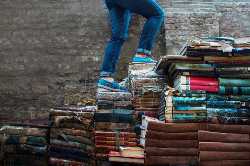 Utbildning begrepp En ung kvinna klättrar upp trappan av böcker fotografering för bildbyråer