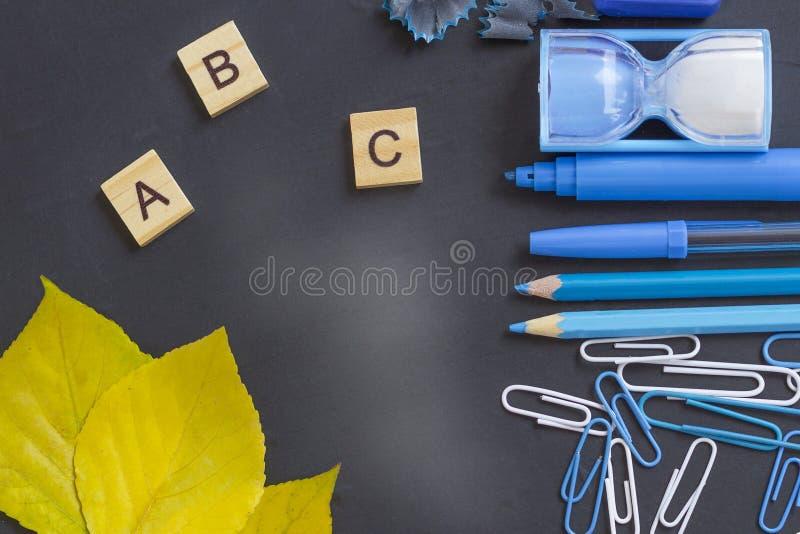 Utbildning eller tillbaka till skolabegreppet Blåa skolatillförsel på svart tavla med kopieringsutrymme arkivbilder