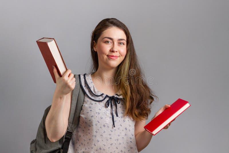 Utbildning En ung kvinna eller tonåring med ryggsäck på ryggen, glatt med böcker i handen royaltyfria bilder