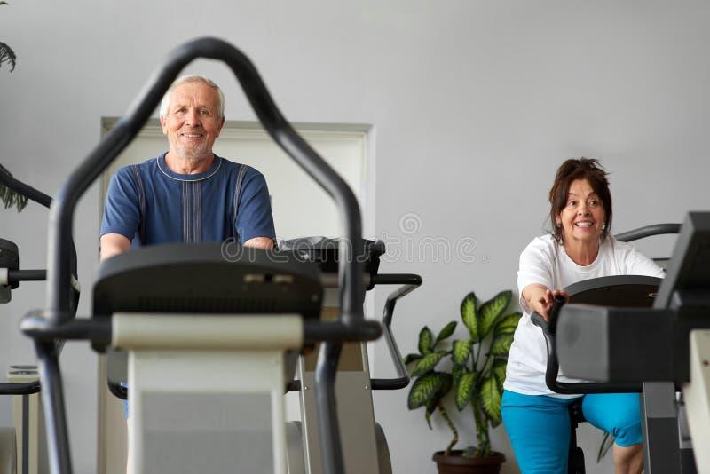Utbildning för äldre man och kvinnapå en stationär cykel royaltyfri foto