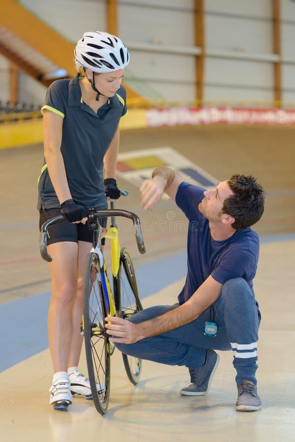 Utbildning för kvinnlig idrottsman nen i velodrome med lagledaren royaltyfria foton