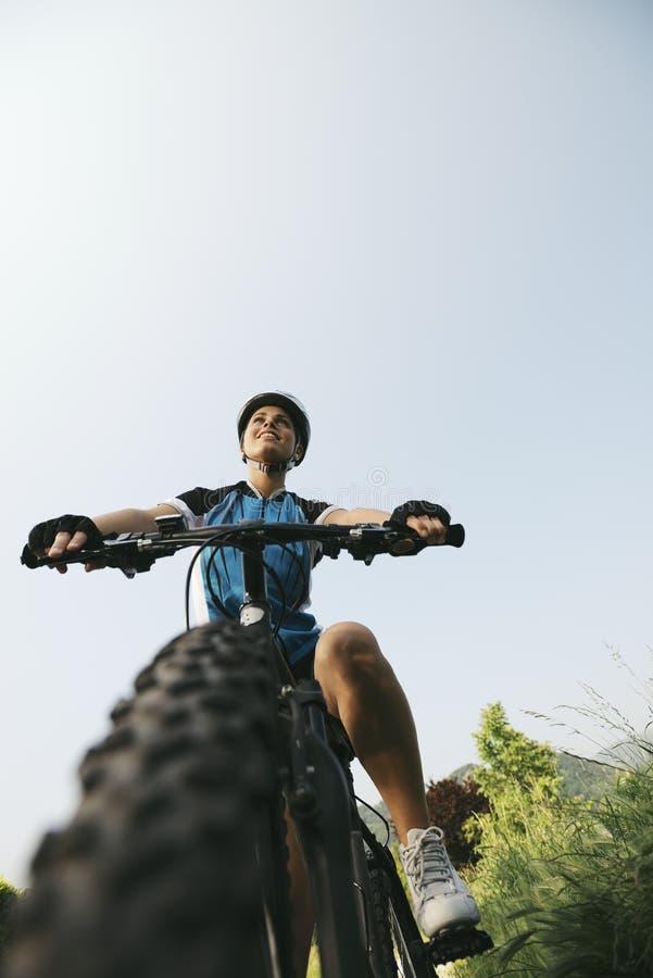 Utbildning för ung kvinna på mountainbiket och att cykla in parkerar arkivbilder