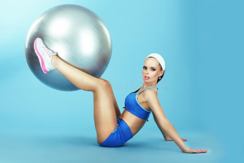 utbildning idrotts- Kvinna i Sportswear med konditionbollen royaltyfri bild