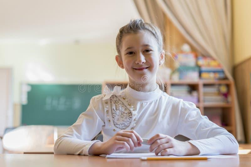 utbildning och skolabegrepp - liten studentflickahandstil i anteckningsbok på skolan royaltyfria bilder