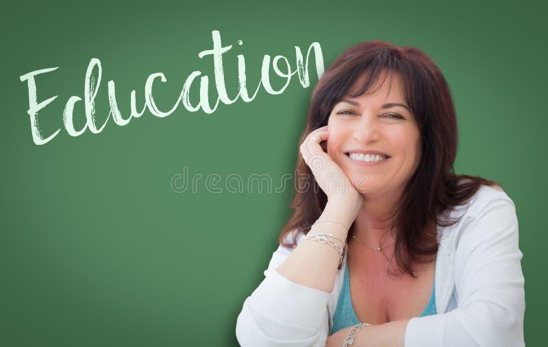 Utbildning som ?r skriftlig p? den gr?na svart tavlan bak att le kvinnan royaltyfria bilder