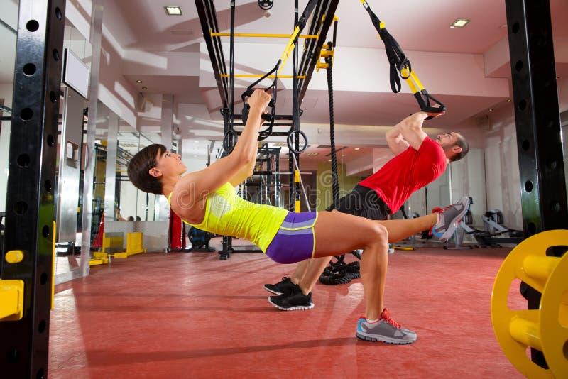 Utbildningsövningar för kondition TRX på den idrottshallkvinnan och mannen arkivfoto