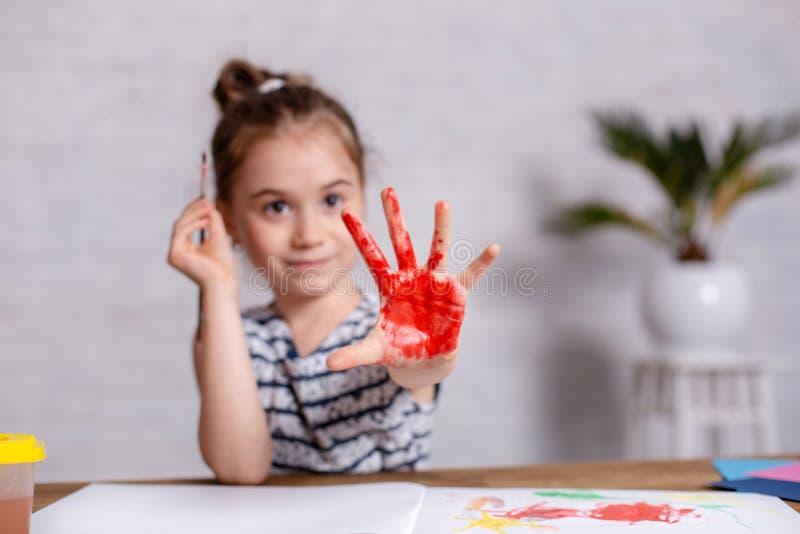 Utbildnings-, skola-, konst- och målningbegrepp - le den lilla studentflickan som visar målade händer på skola arkivfoton