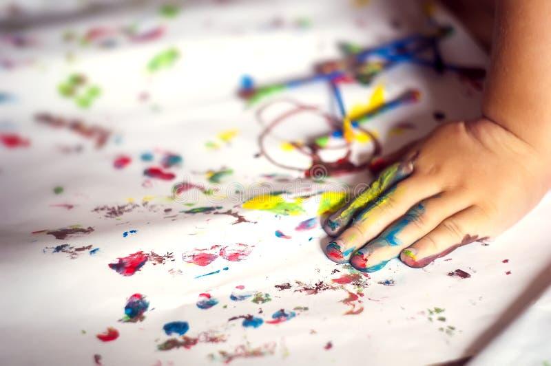 Utbildnings-, skola-, konst- och painitngbegrepp - målade händer för liten flicka visning arkivbild