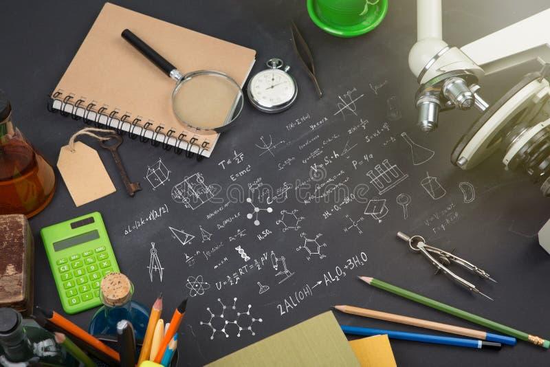 Utbildningsbegrepp - b?cker, mikroskopet och vetenskap skissar p? svart tavla royaltyfri bild