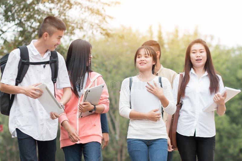 Utbildningsbegrepp: Förtroliga asiatiska studentgrupper som går i handböcker, bärbara datorer på utsidan av klassrummet på univer arkivfoton