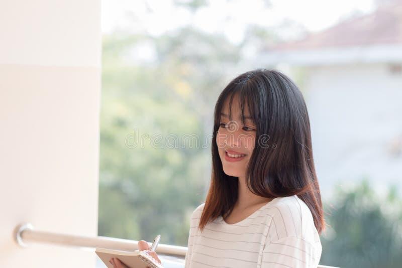 Utbildningsbegrepp: Glad asiatisk, söt kvinnlig student som leker och noterar att hon studerar tidtabellen för kontroll av arkivfoton