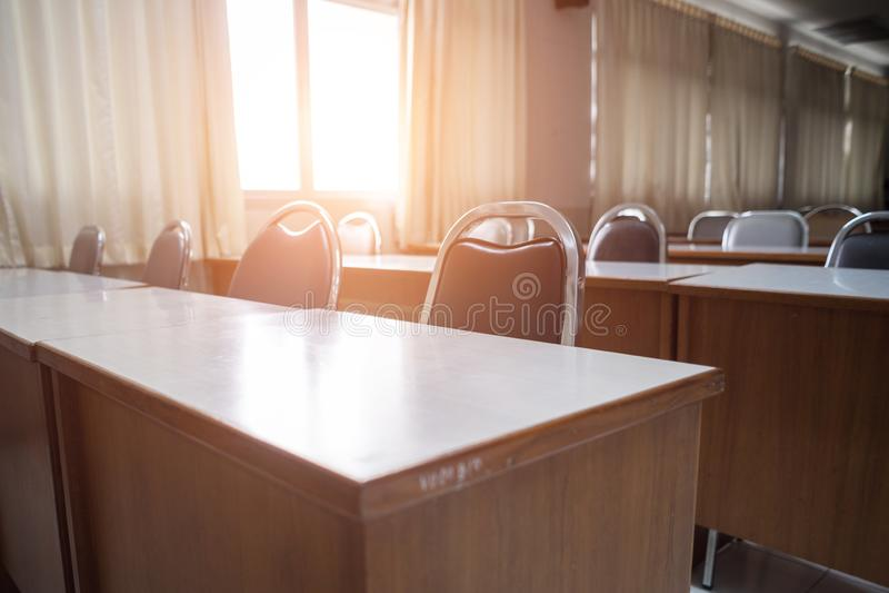 Utbildningsbegrepp: Tomt högskola- eller universitetklassrum med trätabeller och stolar i rad utan studenten eller läraren i roen arkivbild