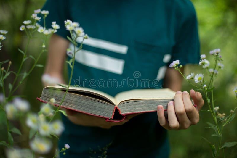 Utbildningsbegrepp - tonåringen rymmer en bok i hans händer i natur arkivbild
