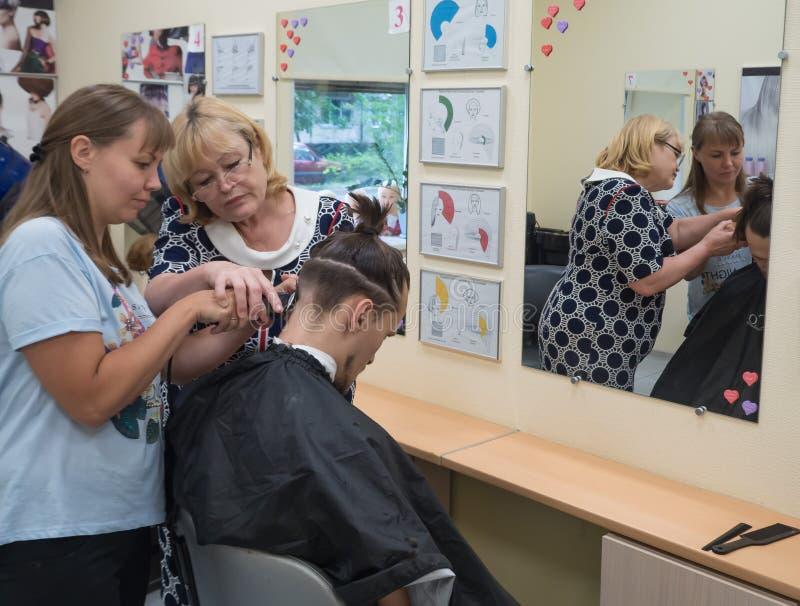 Utbildningsfrisyr Läraren undervisar studentmanfrisyrerna Ryssland St Petersburg royaltyfri fotografi