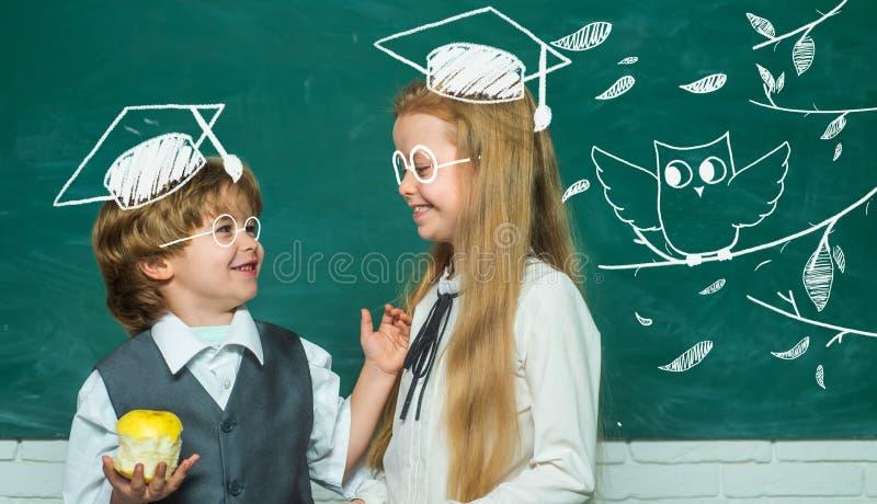 utbildningsillustrationungar st?llde in vektorn Flicka och pojke med lyckligt framsidauttryck nära skrivbordet med skolatillförse arkivfoton