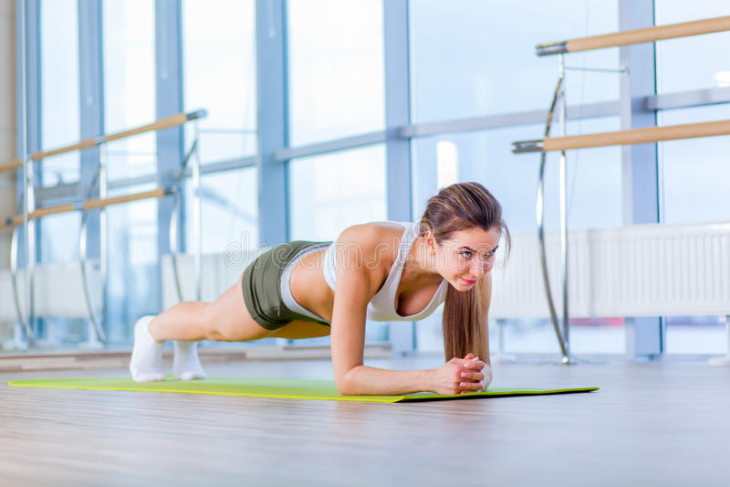 Utbildningskonditionkvinna som gör plankakärnaövningen som utarbetar för tillbaka sport för inbindnings- och ställingsbegreppspil royaltyfria foton