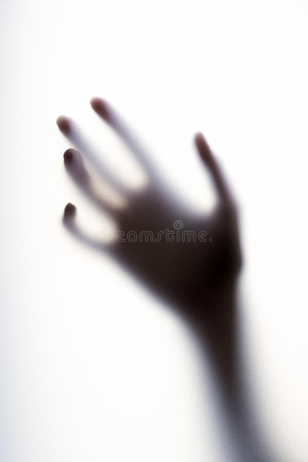 Utbredd skugga av handen med tunna fingrar bak det frostade exponeringsglaset arkivbilder