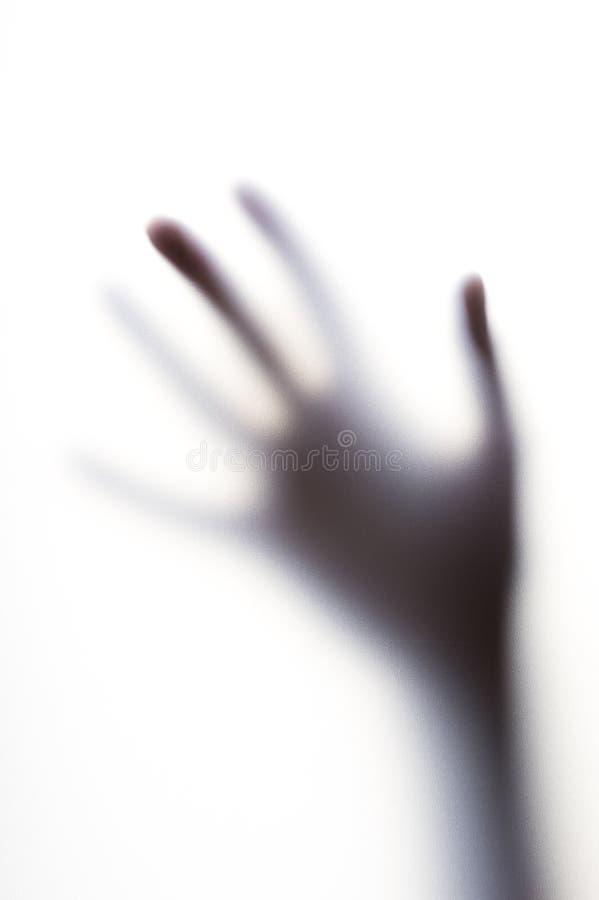 Utbredd skugga av handen med tunna fingrar bak det frostade exponeringsglaset royaltyfri foto