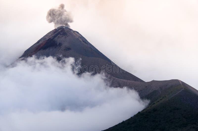 Utbrott av vulkan Fuego i molnigt och dimmigt väder royaltyfria bilder