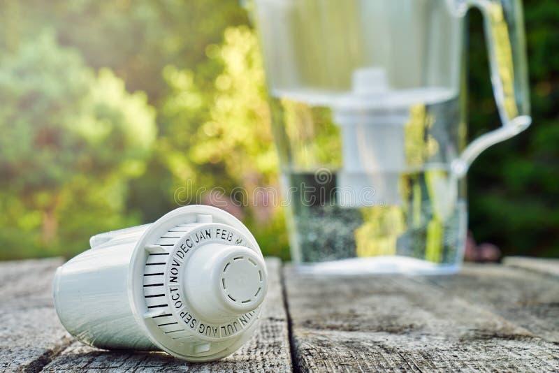 Utbytbar kassett och en tillbringare för vattenfilter på träbrädena i sommarträdgården royaltyfri foto