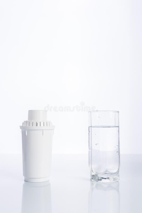 Utbytesvattenfilter och exponeringsglas av renat vatten på vit bakgrund, reflexion royaltyfria foton