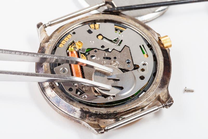 Utbytning av batteriet i kvartsklocka vid pincett royaltyfria bilder