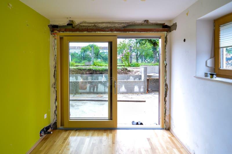 Utbytning av tegelstenväggen med den glass glidningsdörren i bostads- hous arkivfoto