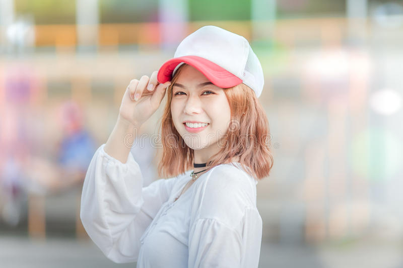 Utdoor portrait of a young beautiful fashionable happy smilng lady posing on Model wearing hat cap and stylish clothes . Girl loo royalty free stock photography