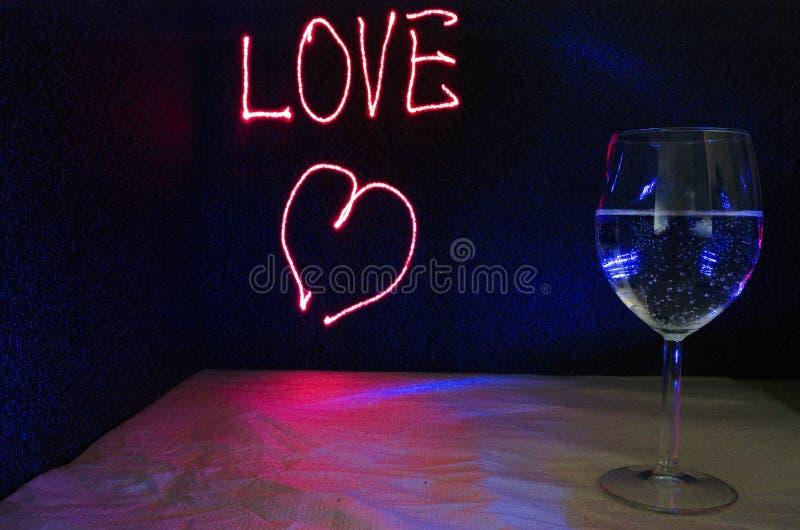 Utdraget förälskelsetecken för laser för bakgrund med glas av bubbladrinken för parti och beröm av valentindagen arkivfoton
